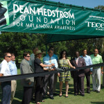 Jack Amor, at center in the blue shirt and tie, prepares to cut the ribbon to dedicate a new sun shade in Tampa.