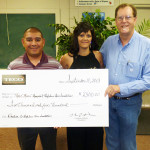 From left, Thad Lopez, Tracy Moore and Clyde Roberds at the presentation of a $2.500 check in donations from TECO team members to Moore's nonprofit Highline Hero Foundation.
