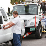 TECO team members apply Tampa Bay Lightning stickers to company fleet vehicles.