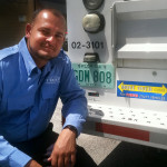 "Chris Furlow at his truck with its ""Move Over Florida"" bumper sticker."
