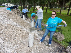 "Volunteers - several in their ""We Care"" TECO volunteer T-shirt - shovel oyster shells into bags."