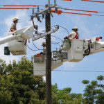 Tampa Electric team members install a recloser.