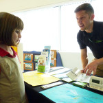 Ian Sprawls works to persuade a young Mega Night attendee that Energy Planner is ideal for her home.
