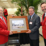 Johnny Dean Page, Gordon Gillette and Doug Driggers, regional manager with TECO's Community Relations team, with the rendering of Johnny Dean Page Substation at the Florida Strawberry Festival Annual Parade Luncheon.